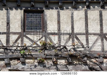 Old framework house at main square of medieval village Perouges in France