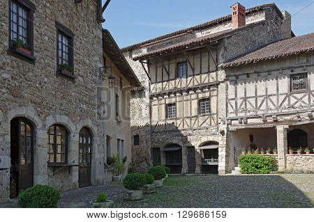 Old framework houses at main square of medieval village Perouges in France