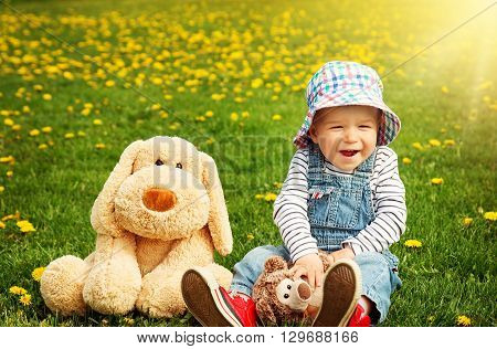 Little boy in hat standing on the field with soft toys in summer