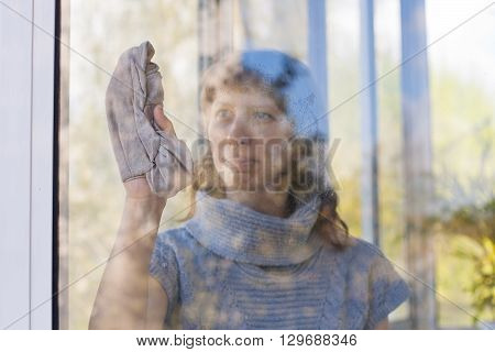 young woman washing window in the room