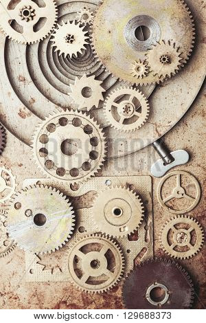 Steampunk background from mechanical clocks details over old metal background. Inside the clock, gears