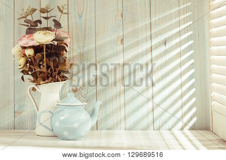 Morning still life on shabby chic table and light from the blinds