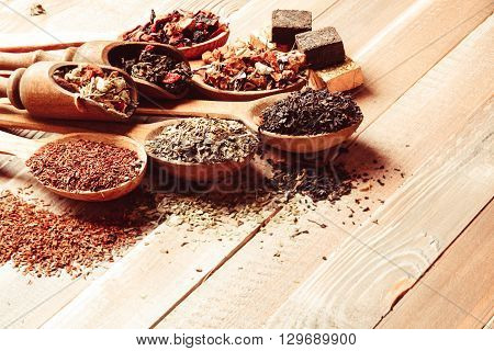 Various of dried tea in wooden scoops and spoons