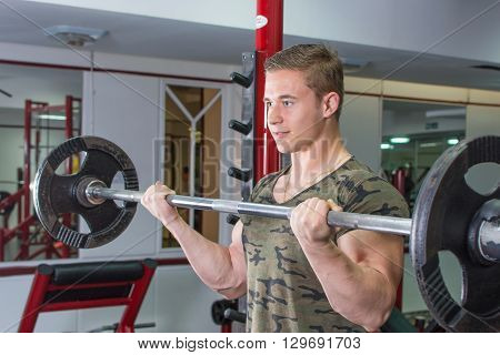 Man Performing Barbell Curl At The Gym