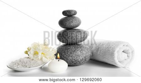 Spa still life with pebbles and candlelight isolated on white