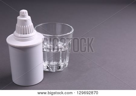 Filter cartridge and a glass of water on grey background