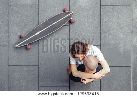 Top view of fashionable couple of man and woman hugging on a concrete surface near longboard. Outdoors, lifestyle. Fashionable couple shoot in a urban location.