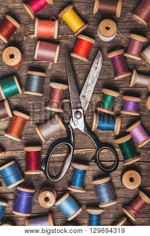 Retro wooden sewing spools with colourful threads and vintage scissors