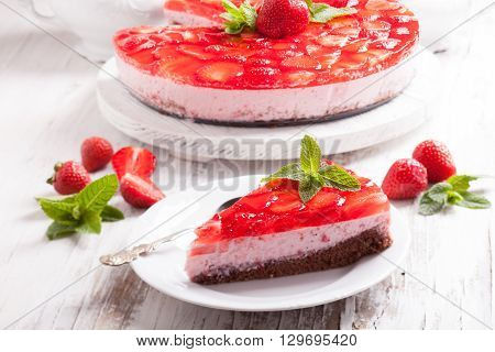 Strawberry cake on white wooden plate with mint leaf