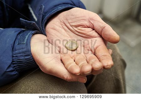 hands of beggar with one euro coin begging for money