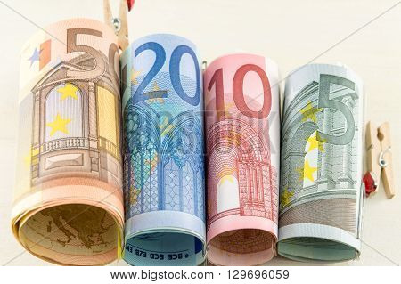 Rolled up euro bills on a wooden table