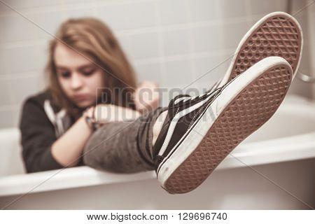 Teenage Girl In Black Sneakers Sits In Bath
