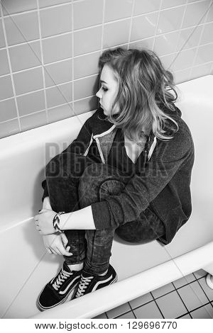 Stressed Sad Blond Teenage Girl Sitting In Empty Bath