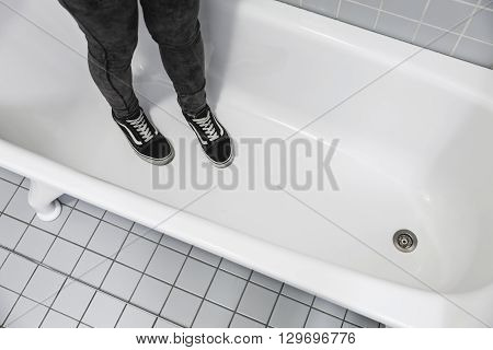 Teenager In Sporty Sneakers Stands In White Bath