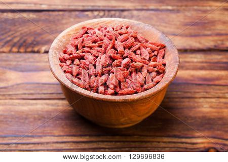 Red dried goji berries in a wooden bowl