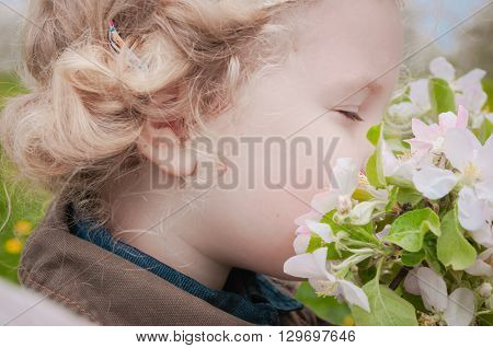 little Caucasian girl enjoying the aroma of apple blossoms