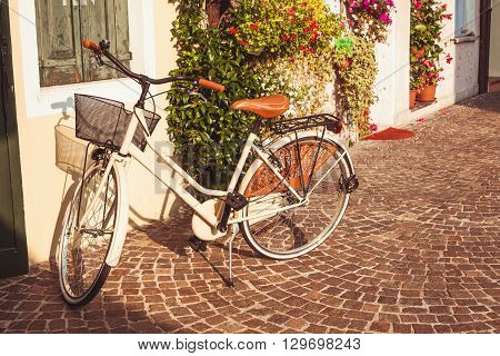 White vintage bicycle with basket on vintage house wall in Italy