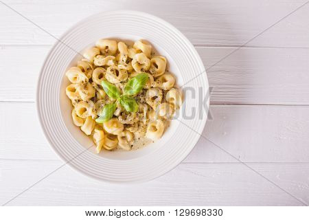 Delicious dish of tortellini with pesto in white plate. Top view