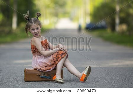 Funny little girl sitting on a suitcase on the road.
