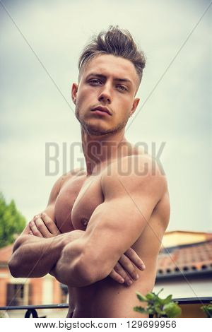 Handsome shirtless muscular young man outdoor, looking at camera, arms crossed on chest