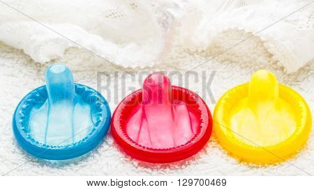 Healthcare medicine contraception and birth control. Closeup colorful condoms with lace lingerie.