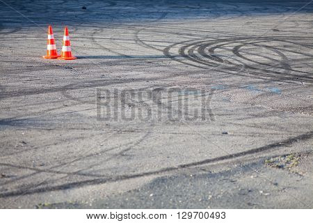 Color image of two traffic cones on tarmac.