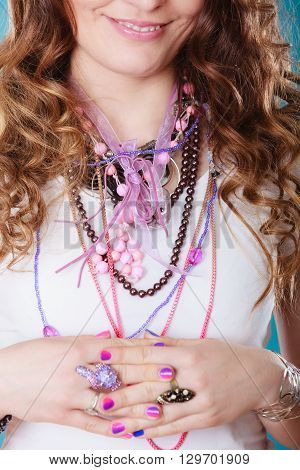 Closeup of woman wearing many plenty of jewelry rings necklaces beads.