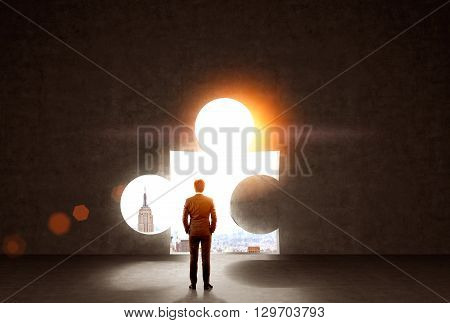 Businessman standing against wall with puzzle piece hole and sunlit New York city view