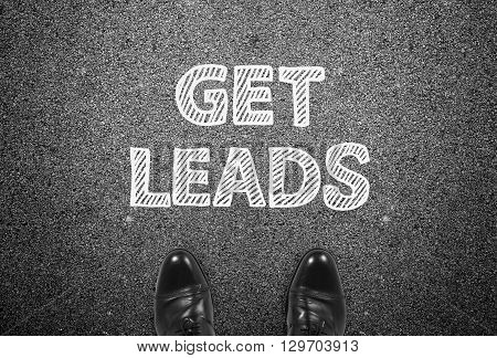 Get leads writing on ground with businessman feet