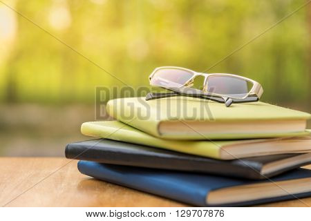Glasses with diary on wood table with nature background