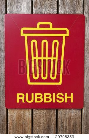 Red garbage bin sign on a wooden bin.
