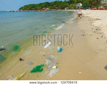Sihanoukville Cambodia - Mar 19 2015 : Tourist walking along garbage on dirty beach