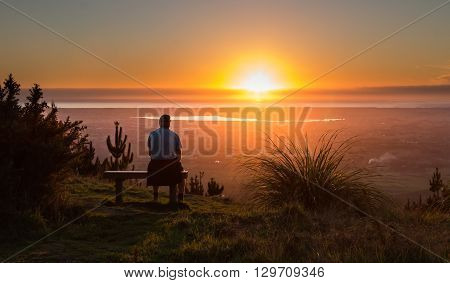 Man on a seat watching the sun go down over the town of Levin New Zealand