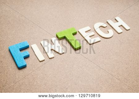Text 'FinTech' wording on brown background - FinTech colorful uppercase letter made from wood