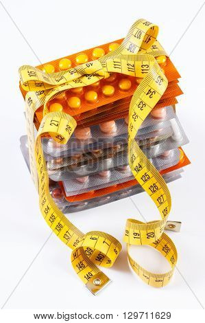 Blisters of medical pills tablets capsules or supplements wrapped tape measure concept of treatment health care healthy lifestyle and slimming