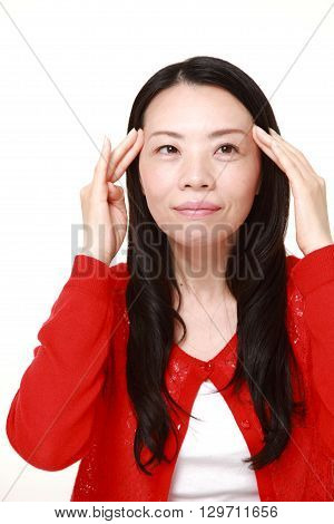 portrait of young Japanese woman doing self head massage on white background