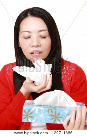 portrait of woman with an allergy sneezing into tissue on white background