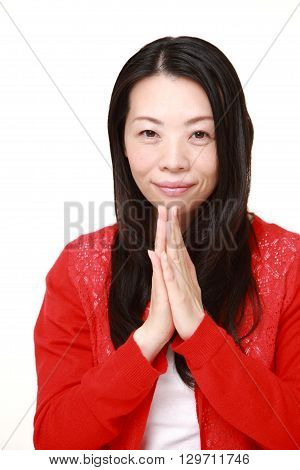 portrait of woman folding her hands in prayer on white background