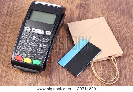 Credit card reader payment terminal with contactless credit card and paper shopping bag cashless paying for shopping finance concept