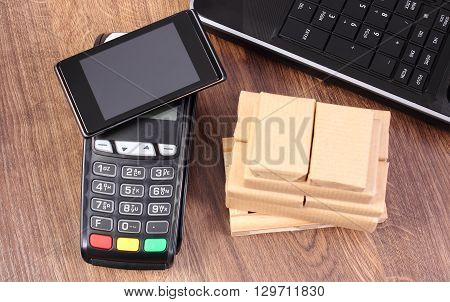 Credit card reader payment terminal with mobile phone with NFC technology laptop and small wrapped boxes on wooden pallet cashless paying for products and shipping