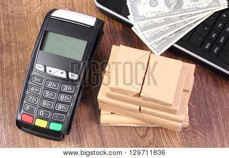 Credit card reader payment terminal with currencies dollar laptop and small wrapped boxes on wooden pallet cashless or cash paying for products and shipping