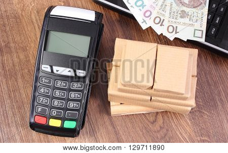 Credit card reader payment terminal with polish currency money laptop and small wrapped boxes on wooden pallet cashless or cash paying for products and shipping