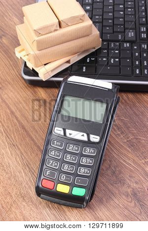Credit card reader payment terminal laptop and small wrapped boxes on wooden pallet cashless paying for products and shipping finance concept