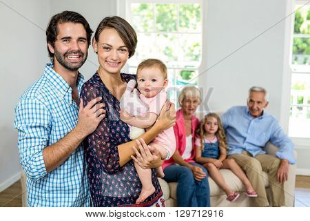 Portrait of happy family with grandparents sitting in background at home