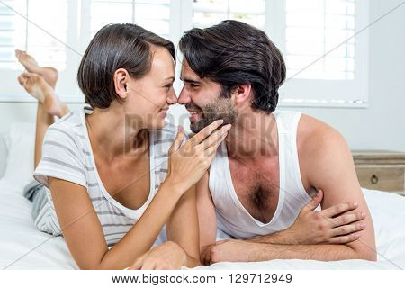 Close-up of happy couple lying on bed at home