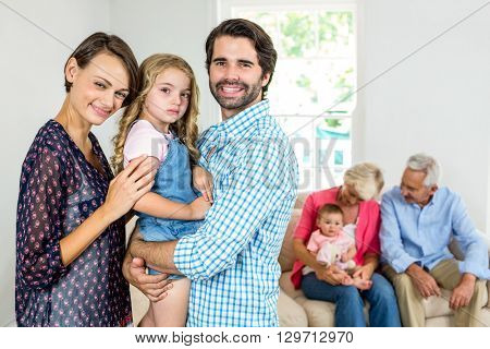 Portrait of family smiling while grandparents sitting in background at home