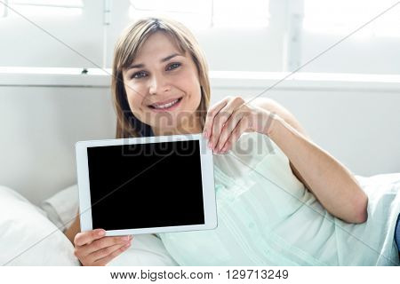 Portrait of beautiful woman showing digital tablet while relaxing on bed