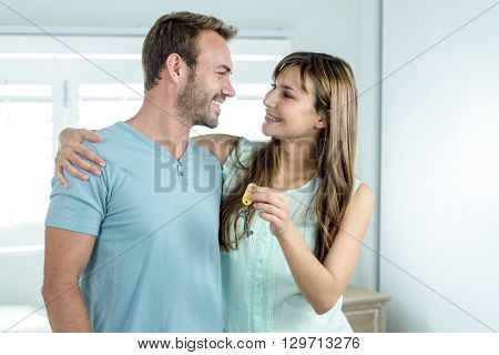 Happy couple with new house key embracing against window