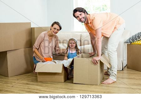 Happy family unpacking boxes while relocating in new house