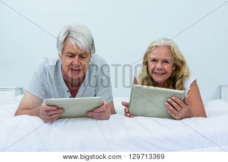 Senior couple using digital tablets while relaxing in bedroom at home